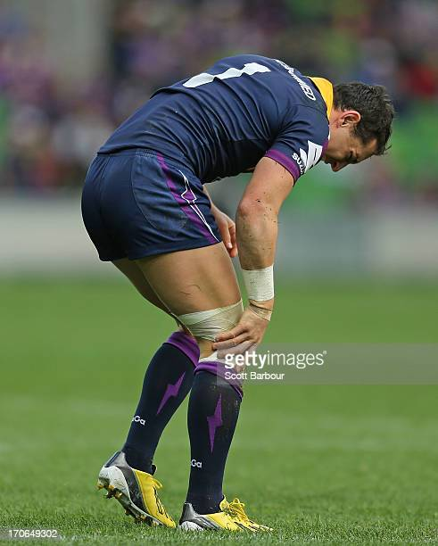 Billy Slater of the Storm holds his knee after injuring it in the first half during the round 14 NRL match between the Melbourne Storm and the...