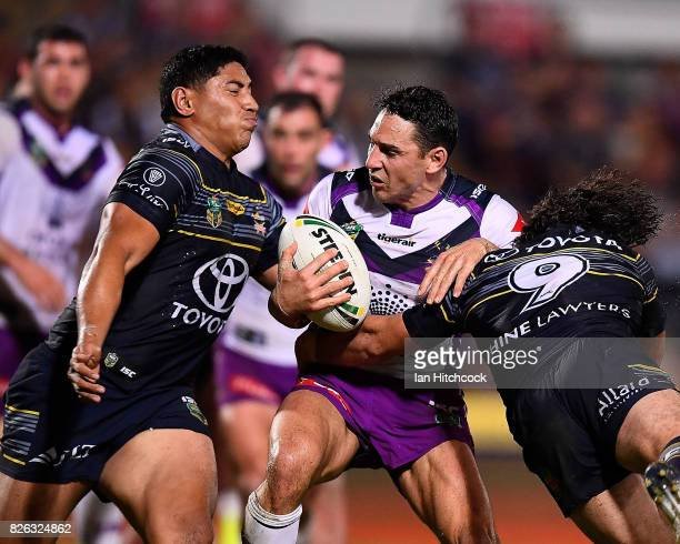 Billy Slater of the Storm is tackled by Jason Taumalolo and Jake Granville of the Cowboys during the round 22 NRL match between the North Queensland...