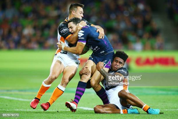 Billy Slater of the Storm is tackled by Luke Brooks of the Tigers and Kevin Naiqama during the round two NRL match between the Melbourne Storm and...