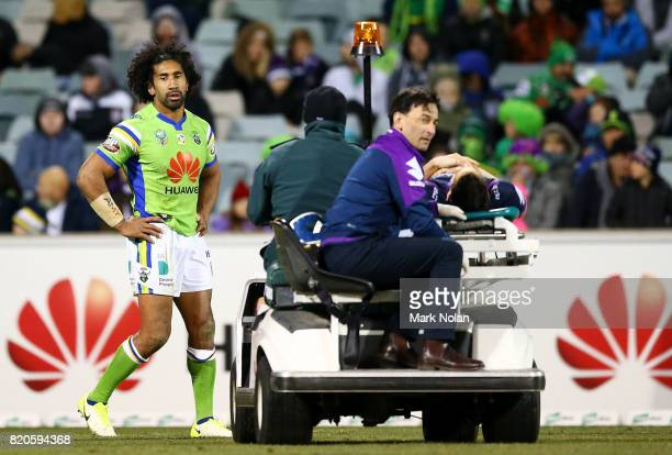 Billy Slater of the Storm is taken from the field after a tackle by Iosia Soliola of the Raiders during the round 20 NRL match between the Canberra...