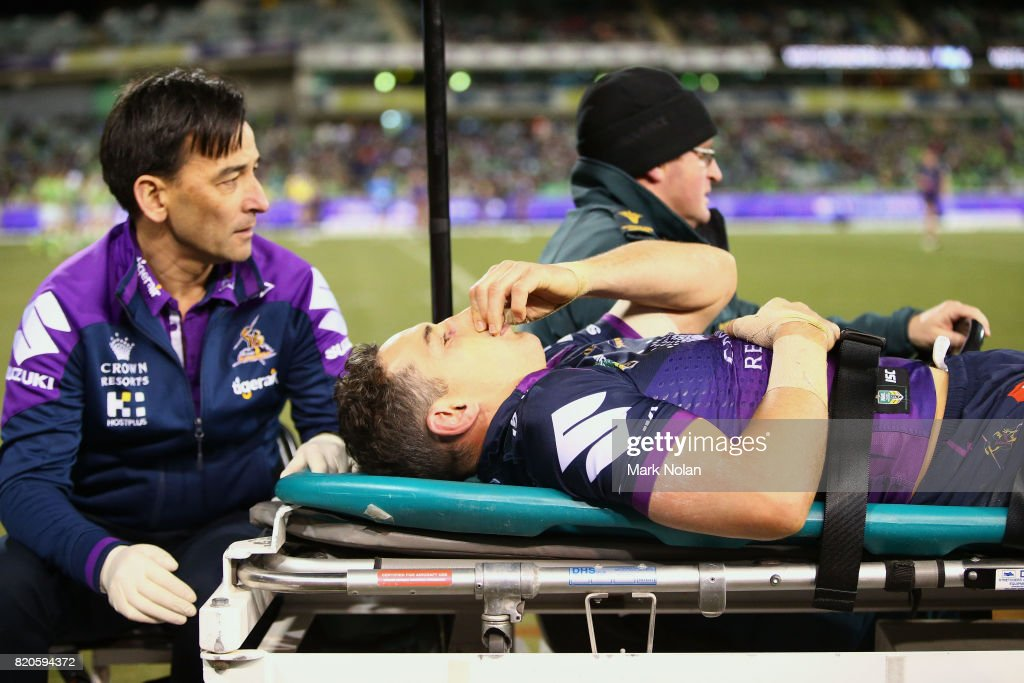 Billy Slater of the Storm is taken from the field after a tackle by Iosia Soliola of the Raiders during the round 20 NRL match between the Canberra Raiders and the Melbourne Storm at GIO Stadium on July 22, 2017 in Canberra, Australia.