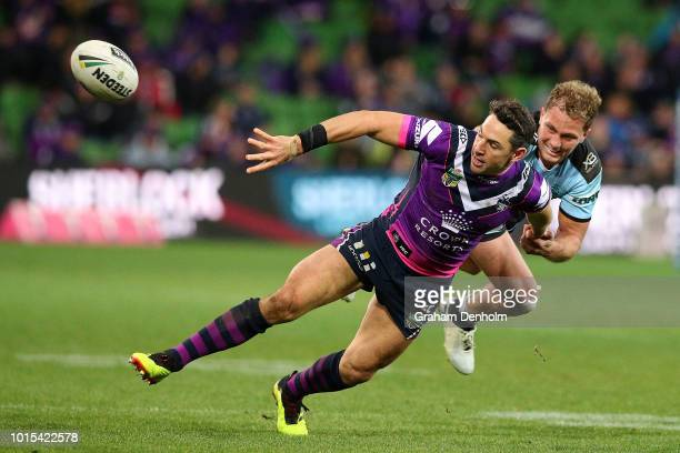 Billy Slater of the Storm passes as he is tackled during the round 22 NRL match between the Melbourne Storm and the Cronulla Sharks at AAMI Park on...