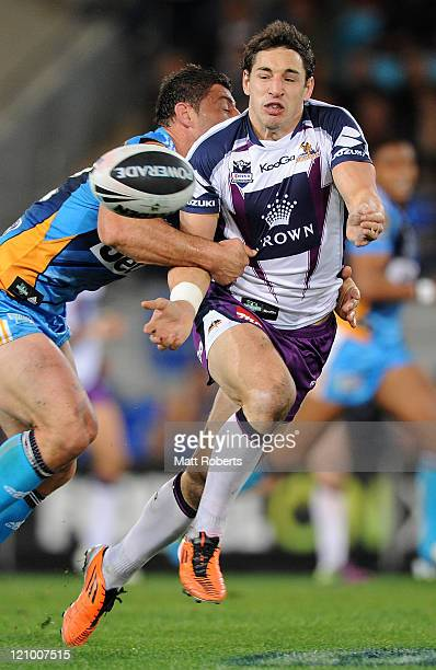 Billy Slater of the Storm passes the ball in the tackle during the round 23 NRL match between the Gold Coast Titans and the Melbourne Storm at...