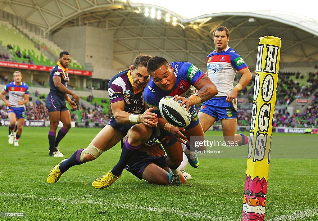 Billy Slater of the Storm performs a try saving tackle on Joey Leilua of the Knights during the round 14 NRL match between the Melbourne Storm and the Newcastle Knights at AAMI Park on June 16, 2013 in Melbourne, Australia.