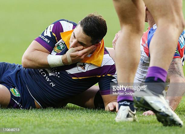 Billy Slater of the Storm reacts and feels his face after a contest with Darius Boyd of the Knights during the round 14 NRL match between the...