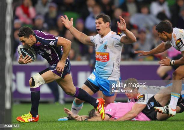 Billy Slater of the Storm runs in for a try as the referee falls over during the round 23 NRL match between the Melbourne Storm and the Gold Coast...