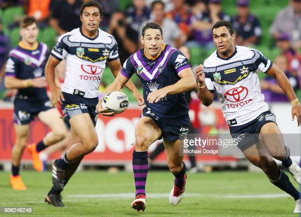 Billy Slater of the Storm runs with the ball from Justin O'Neill of the Cowboys during the round three NRL match between the Melbourne Storm and the...