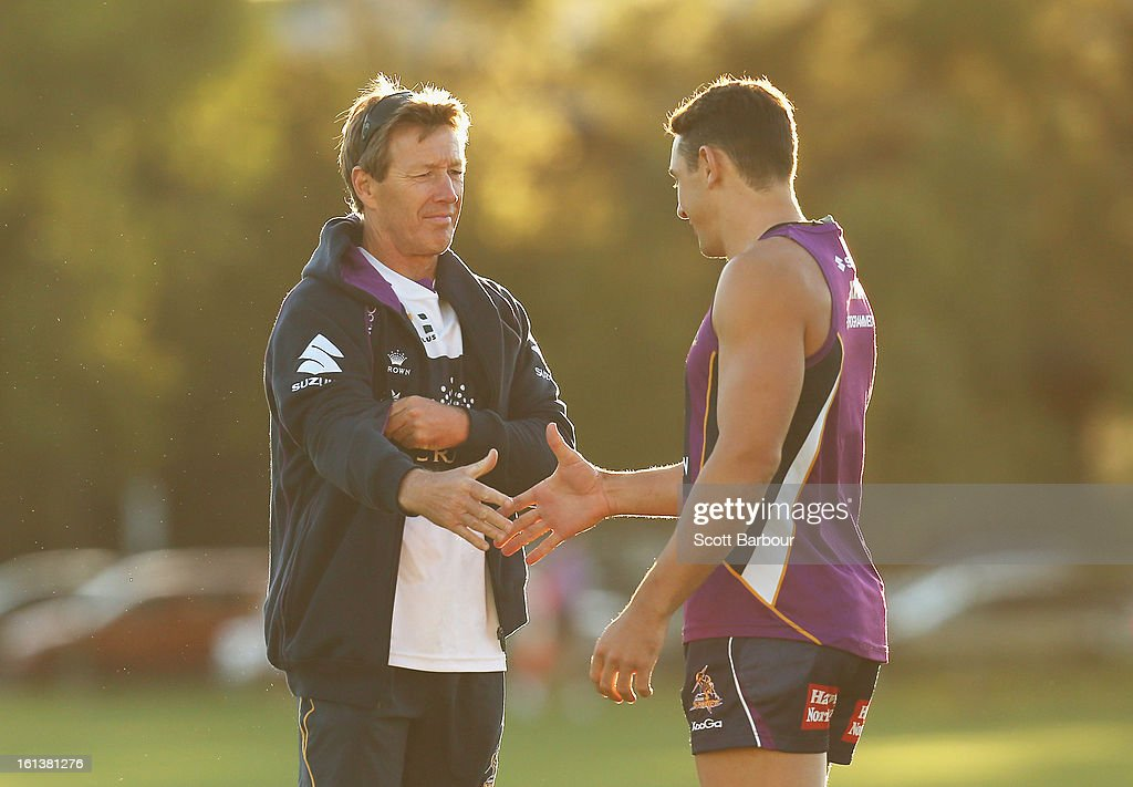 Billy Slater of the Storm shakes hands with Storm coach Craig Bellamy (L) as they arrive at a Melbourne Storm NRL training session at Gosch's Paddock on February 11, 2013 in Melbourne, Australia.