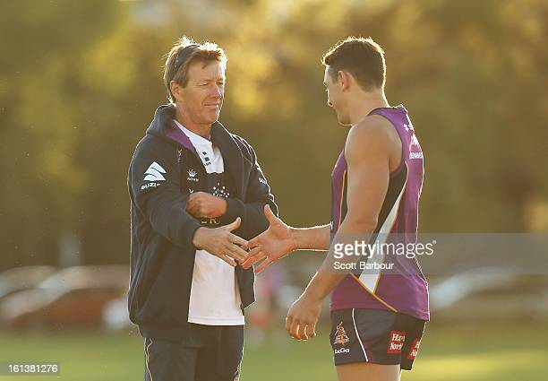 Billy Slater of the Storm shakes hands with Storm coach Craig Bellamy as they arrive at a Melbourne Storm NRL training session at Gosch's Paddock on...