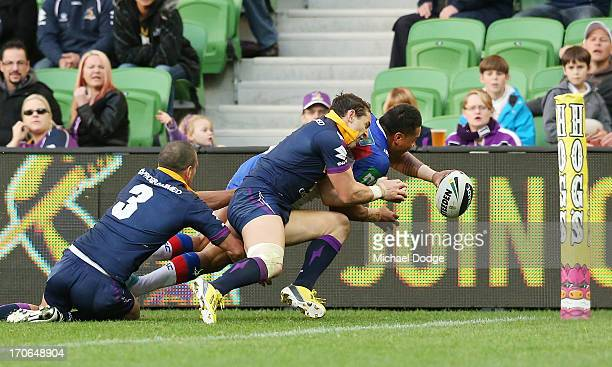 Billy Slater of the Storm stops a potential try from Joey Leilua of the Knights during the round 14 NRL match between the Melbourne Storm and the...