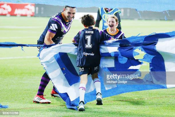 Billy Slater runs out through the banner with hisÊÊtwo children daughter Tyla Rose and son Jake for this 300th match during the round two NRL match...