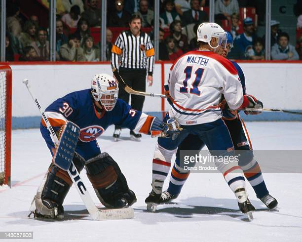 Billy Smith of the New York Islanders attempts to see past the screen of Ryan Walter of the Montreal Canadiens Circa 1982 at the Montreal Forum in...