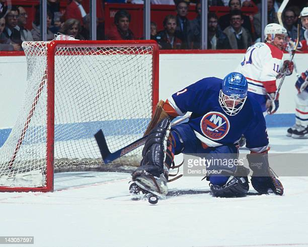 Billy Smith of the New York Islanders keeps the puck out of the net with his skate during a game against the Montreal Canadiens Circa 1980 at the...
