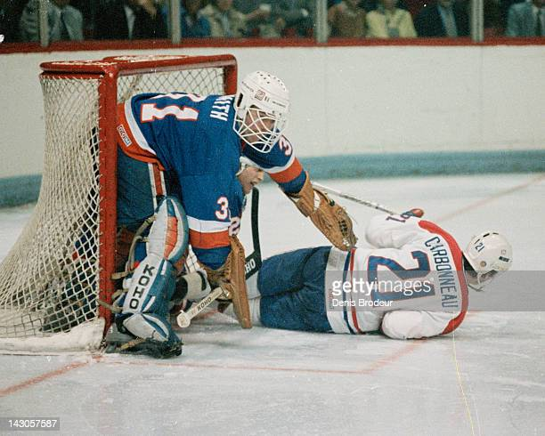 Billy Smith of the New York Islanders knocks down Guy Carbonneau of the Montreal Canadiens as he skates through the crease Circa 1980 at the Montreal...