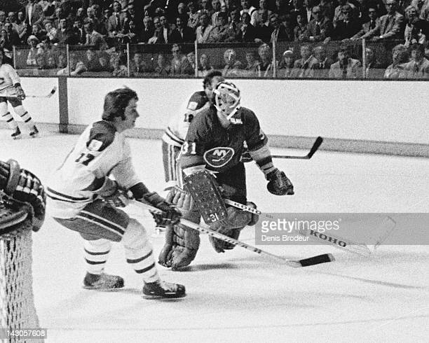 Billy Smith of the New York Islanders races for the puck against two of the Montreal Canadiens players Circa 1980 at the Montreal Forum in Montreal...