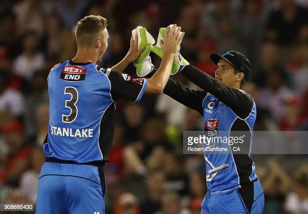Billy Stanlake and Alex Carey of the Strikers celebrate after taking the wicket of Marcus Harris of the Renegades during the Big Bash League match...