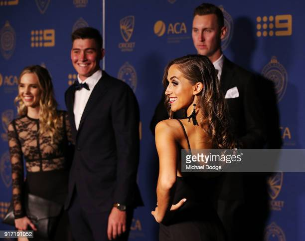 Billy Stanlake watches partner Maddison Lochert pose at the 2018 Allan Border Medal at Crown Palladium on February 12 2018 in Melbourne Australia