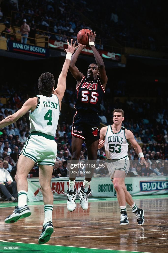 Billy Thompson #55 of the Miami Heat shoots a jump shot against Jim Paxson #4 and Joe Kleine #53 of the Boston Celtics during a game played in 1990 at the Boston Garden in Boston, Massachusetts.