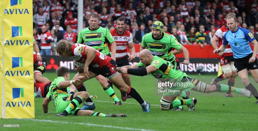 Billy Twelvetrees of Gloucester breaks away from Sam Dickinson (R) to score their fourth try during the Aviva Premiership match between Gloucester Rugby and Northampton Saints at Kingsholm Stadium on October 7, 2017 in Gloucester, England.