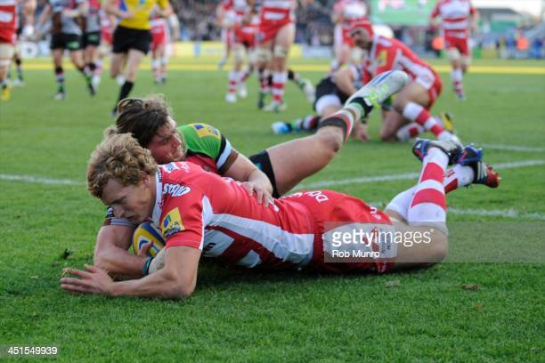Billy Twelvetrees of Gloucester Rugby dives over to score a try despite the efforts of Luke Wallace of Harlequins during the Aviva Premiership Rugby...