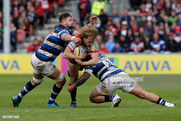 Billy Twelvetrees of Gloucester tackled by Elliott Stooke and Anthony Perenise of Bath during the Aviva Premiership match between Gloucester Rugby...