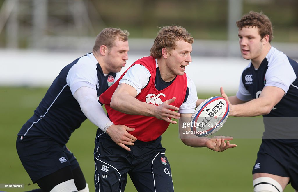Billy Twelvetrees passes the ball as James Haskell (L) and Joe Launchbury tackle during the England training session held at St Georges Park on February 14, 2013 in Burton-upon-Trent, England.