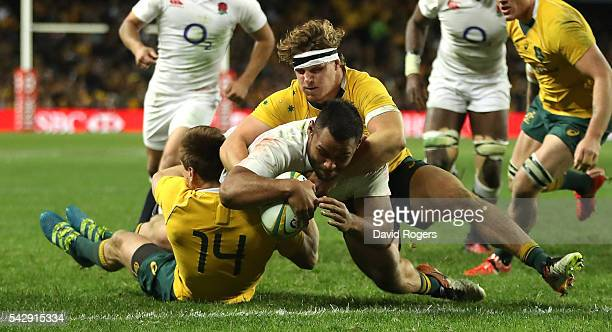 Billy Vunipola of England holds off Dane HaylettPetty and Michael Hooper to score their third try during the International Test match between the...