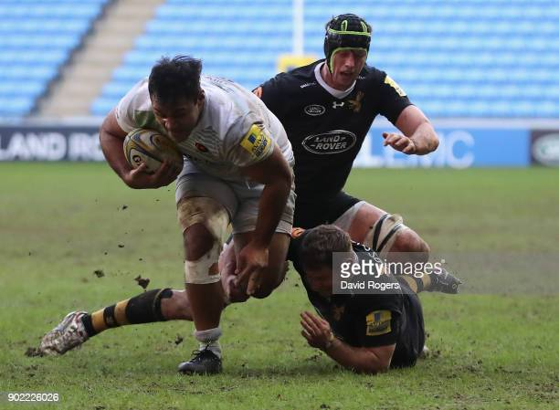 Billy Vunipola of Saracens charges away from Thomas Young and James Gaskell during the Aviva Premiership match between Wasps and Saracens at The...