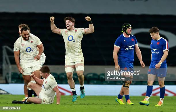Billy Vunipola, Owen Farrell and Tom Curry of England celebrate victory at the final whistle as Gregory Alldritt of France looks on dejected during...