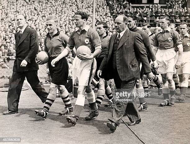 Billy Wright captain of Wolverhampton Wanders and Norman Plummer captain of Leicester City FC lead out their teams prior to the start of the FA Cup...