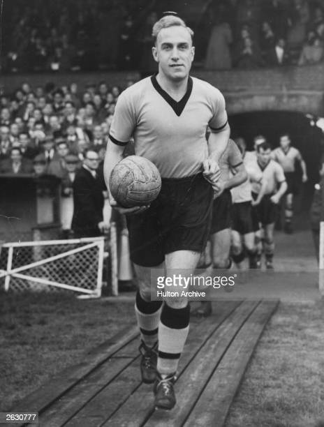 Billy Wright the English footballer leading the Arsenal team running from the tunnel up to the pitch