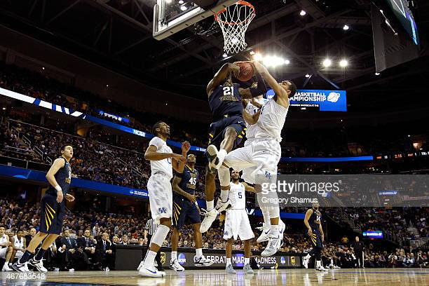 BillyDee Williams of the West Virginia Mountaineers drives to the basket and is blocked by Willie Cauley-Stein and Trey Lyles of the Kentucky...