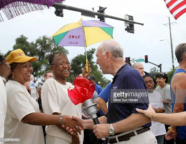 Biloxi Mayor AJ Holloway shakes hands with second liners during a celebration following the Bacot McCarty Foundation Coastal Torch Relay at the foot...
