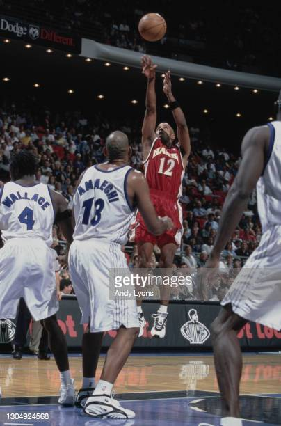 Bimbo Coles, Point Guard for the Atlanta Hawks prepares to make a 3 point jump shot as John Amaechi and Ben Wallace look on during their NBA Atlantic...