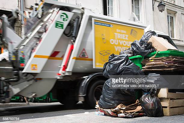 A bin lorry passes by overflowing rubbish bins on June 8 2016 in a street in Paris Two days before the start of Euro 2016 in France rubbish piled up...