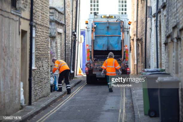 bin men, rubbish collectors or garbage men collecting household waste and recycling in the market town of cirencester, in the cotswolds - garbage truck stock pictures, royalty-free photos & images