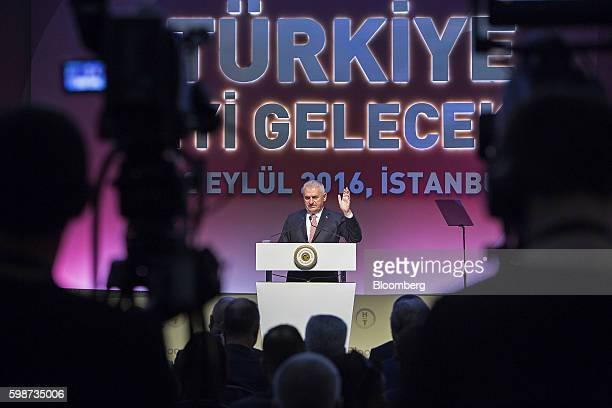 Binali Yildirim Turkey's prime minister gestures as he speaks to an audience during the BloombergHT investor conference in Istanbul Turkey on Friday...