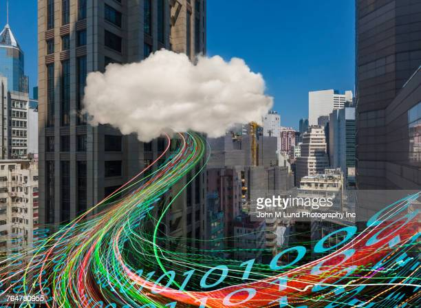 Binary code flowing from cloud hovering in city