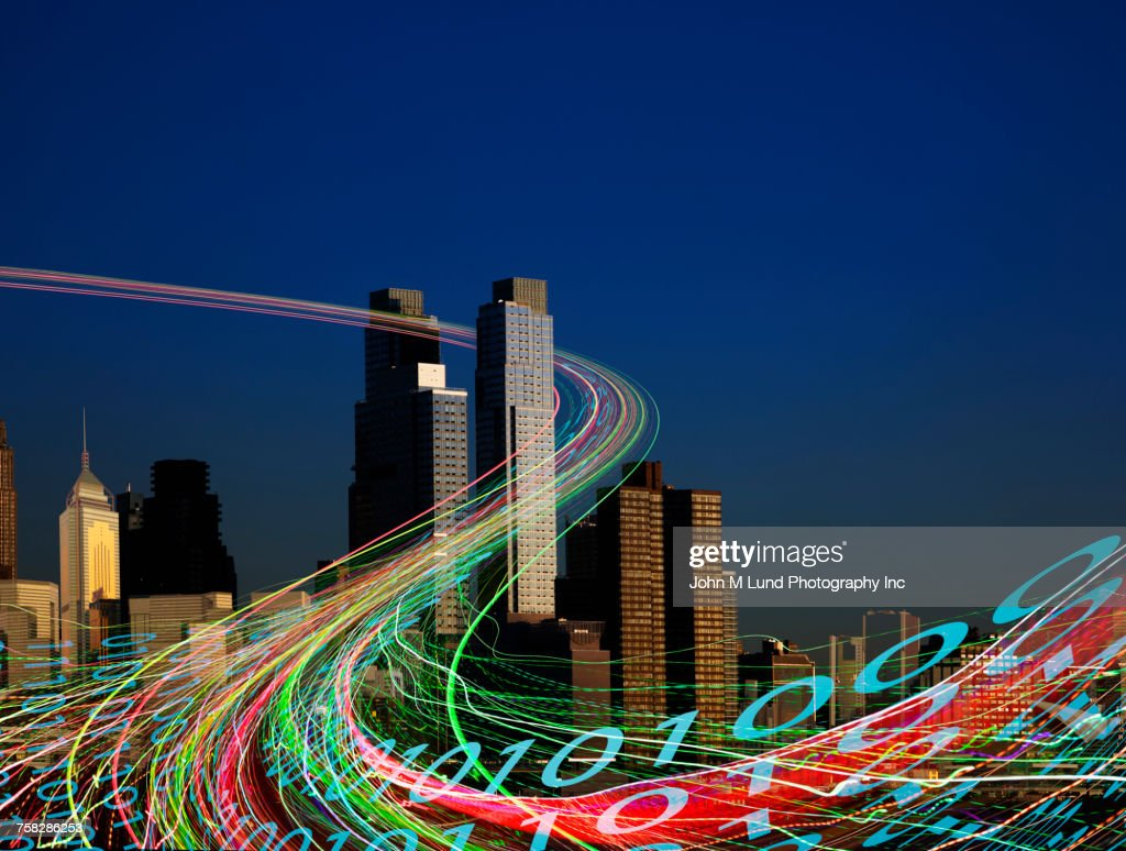Binary code flowing in cityscape at night : Stock Photo