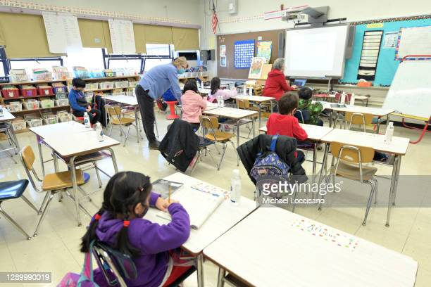 Binasa Musovic , an educational paraprofessional and Chris Frank, a teacher at Yung Wing School P.S. 124, teach blended learning students during the...