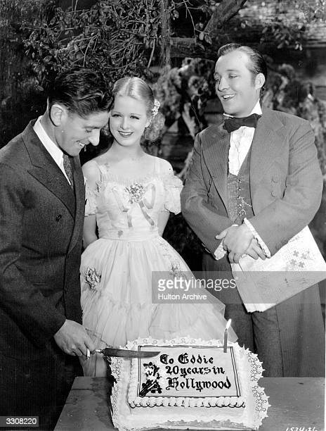 Bing Crosby Joan Bennett and director Edward Sutherland on the set of the Paramount picture 'Mississippi' They are celebrating Edwards 20th year in...