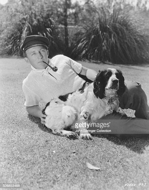 Bing Crosby reclines on a lawn with his pet spaniel and his signature smoking pipe