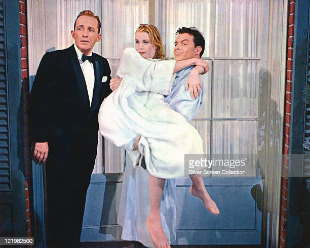 Bing Crosby US singer and actor Grace Kelly US actress being carried by Frank Sinatra US actor and singer in a publicity still from the film 'High...