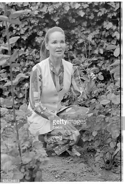Bing Crosby's widow Kathryn admires a rose in her flower garden