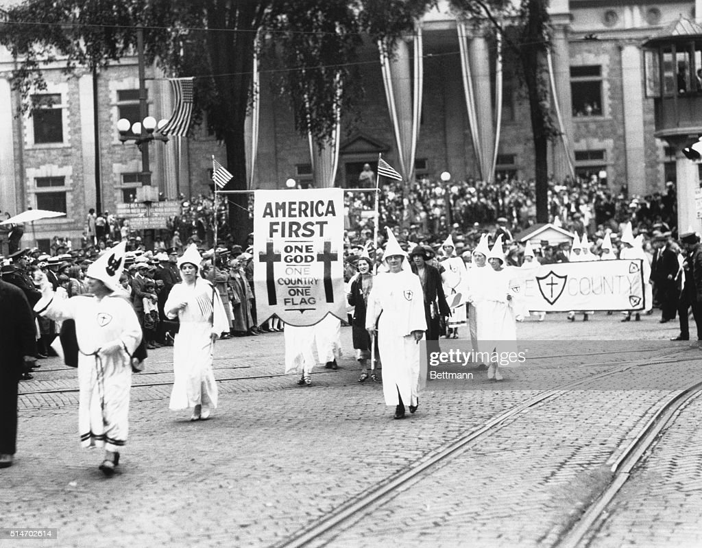 Ku Klux Klan stages an 'America First' parade in Binghamton, NY. Photograph. 1920's.