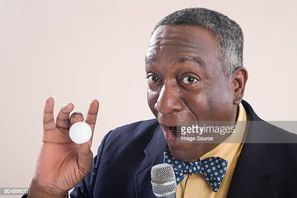 A bingo caller holding a bingo ball