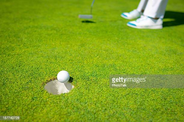 bingo! golfer accurately putting golf ball in the hole - golf flag stock photos and pictures