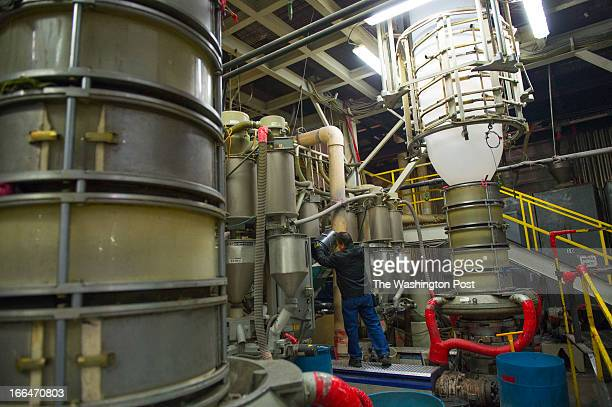 Binh Le junior machine operator loads the plastic extruder with a coloring agent at the Advance Polybag Inc manufacturing plant on March 18 2013 in...
