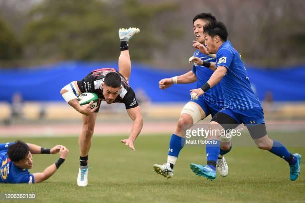 Binjamin Ray Yagi of Munakata Sanix Blues is tackled during the Rugby Top League match between NTT Communications ShiningArcs and Munakata Sanix...