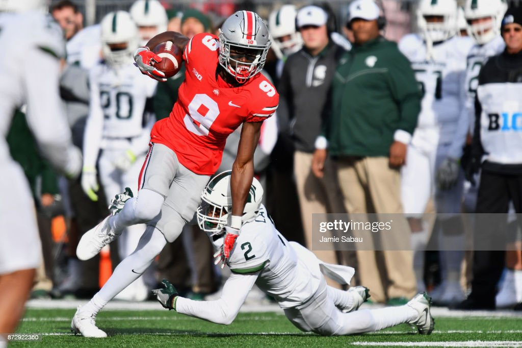 Binjimen Victor #9 of the Ohio State Buckeyes eludes the tackle attempt of Justin Layne #2 of the Michigan State Spartans to pick up additional yardage after a catch in the third quarter at Ohio Stadium on November 11, 2017 in Columbus, Ohio. Ohio State defeated Michigan State 48-3.